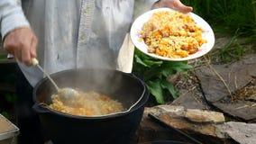 Chef setzt den ursprünglichen Usbekpilaf in eine Schüssel ein Kochen des Usbekpilafs stock video footage