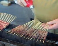 Chef setzte Salz auf Fleisch genanntes Arrosticini in italienischsprachiges ein t ein stockfotos