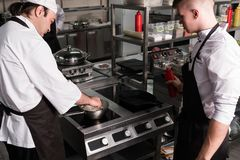 Chef sharing experience skills secrets tips. Chef sharing his skills and experience with a young cook. Restaurant cooking secrets and tips stock images