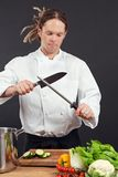 Chef sharpening his knife. Photo of a chef with dreadlocks sharpening his chopping knife royalty free stock photo