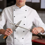 Chef Sharpening Knife In Kitchen Stock Photo