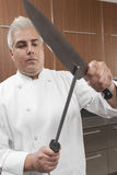 Chef Sharpening Knives In Commercial Kitchen Stock Photography