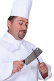 Chef sharpening meat cleaver Royalty Free Stock Photos