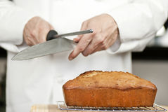 Chef Sharpens Knife Over Banana Bread Stock Images