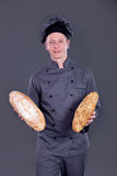 Chef Showing  bread in his hand on a gray background Royalty Free Stock Photos