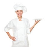 Chef showing empty plate. Happy smilng portrait of female in chef uniform and chef hat isolated on white background. Asian Caucasian woman model Stock Photo