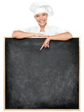 Chef showing menu sign. Blackboard smiling happy. Empty menu chalkboard with copy space for text. Female chef, baker or cook isolated on white background. Mixed Royalty Free Stock Photo