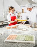 Chef Showing Pasta Tray To Colleague At Kitchen Stock Photography