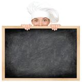 Chef showing restaurant menu. Blackboard - empty blank with copy space for text etc. Funny woman cook peeking over sign. Beautiful happy smiling mixed race Royalty Free Stock Photography