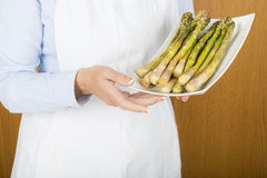 A chef showing a tray with asparagus Royalty Free Stock Photos