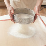 Chef sifting baking powder into dough. For making cake Royalty Free Stock Photo
