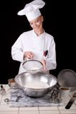 Chef Sifts Cake Flour. Passive posed female Pastry Chef sifting cake flour into a large mixing bowl Stock Image