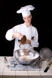 Chef Sifts Cocoa. Action capture of a female Pastry Chef adding cocoa powder into a sieve over a mixing bowl of cake flour Stock Image
