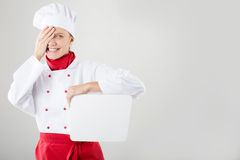 Chef Sign. Woman cook / baker looking over paper sign billboard. Surprised and funny expression woman isolated on white background Royalty Free Stock Photos
