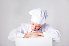 Chef Sign. Woman cook / baker looking over paper sign billboard. Surprised and funny expression woman  on white background Stock Photos