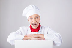 Chef Sign. Woman cook / baker looking over paper sign billboard. Surprised and funny expression woman  on white background Royalty Free Stock Photo