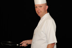 Chef with skillet. Chef in white uniform holding skillet or  frying pan on black background Royalty Free Stock Images