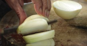 Chef slices the onion. Cutting of onion. Half rings of onions. The hands of the cook. Cut vegetables for Healthy food. 4K stock video footage