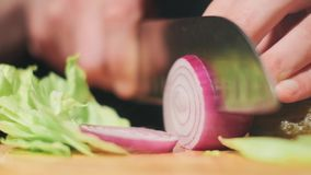 Chef slices the onion. Knife, cutting board, onion. Quick cutting of vegetables. Half rings of onions. bow for frying stock footage