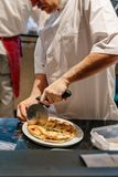 Chef slices a Puccia Al Tarfuto by knife: Thin crispy dough filled with mascarpone, stracciatella, parmesan and black truffle.  stock images