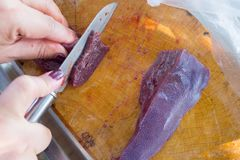 Chef slices raw liver on a cutting board. Chef slices raw liver on a wooden cutting board Stock Photography
