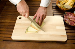 Chef slicing cheese, hands detail Royalty Free Stock Photo