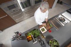 Chef-Slicing Cucumber On-Brett an der Handelsküchenarbeitsplatte Stockbild