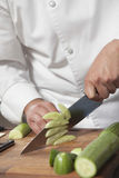 Chef Slicing Cucumber On Chopping Board. Midsection of male chef slicing cucumber on chopping board Royalty Free Stock Photography