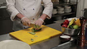 Chef slicing a cucumber finely, medium shot. Chef in restaurant slicing a cucumber finely, medium shot stock video footage