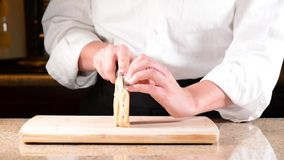 Chef slicing or cutting English Muffin Stock Image