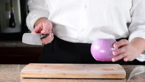 Chef slicing or cutting red onion on cutting board stock footage