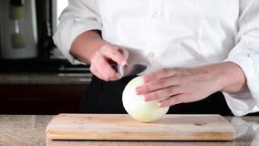Chef slicing or cutting white onion on cutting board stock video footage