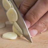 Chef slicing garlic cloves Royalty Free Stock Image