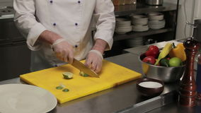Chef slicing a lime, medium shot. Chef in restaurant slicing fresh green lime, medium shot stock video footage