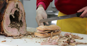 Chef slicing the meat of pork to prepare a sandwich in the food Stock Photo