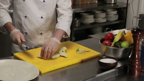 Chef slicing a peer, medium shot. Chef slicing fresh green peer, medium shot stock video footage