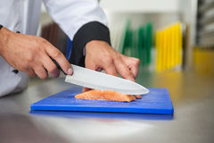 Chef slicing raw salmon with knife on blue cutting board Royalty Free Stock Photo