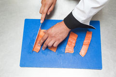 Chef slicing raw salmon with sharp knife Royalty Free Stock Images