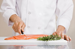 Chef slicing raw salmon to prepare for meal. Chef in chef�s whites slicing raw salmon to prepare for meal Royalty Free Stock Photos