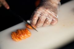 Chef slicing salmon Stock Image