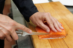 Chef is slicing salmon fillet Stock Photos