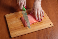 Chef slicing salmon fillet on wooden cutting board. Chef slicing salmon fillet on cutting board Stock Photo