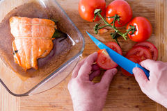 Chef slicing tomatoes to accompany salmon. Close up view from above of the hands of a male chef slicing tomatoes with a blue knife to accompany an oven-baked Stock Photos