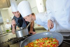 Chef smelling aroma from saucepan stock photos