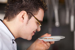Chef Smelling Dish In Kitchen Stock Images