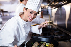 Chef smelling fried fish in the kitchen Stock Photos