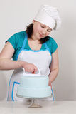 Chef smoothes mastic on the cake Royalty Free Stock Images