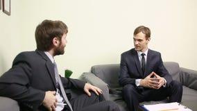 Chef som intervjuar ett manligt sökande i hans kontor dräkter två för affärsmän stock video