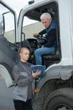 Chef som talar till lastbilsföraren i lager Arkivbilder