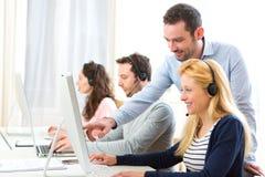 Chef som utbildar ett ungt attraktivt folk på datoren Arkivbild